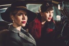 Deux femmes parmi dedans une rétro voiture dans le garage photographie stock libre de droits