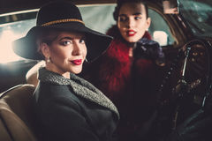 Deux femmes parmi dedans une rétro voiture dans le garage photo libre de droits
