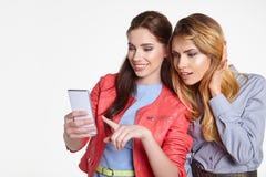 Deux femmes partageant le media social dans un téléphone intelligent Photos libres de droits