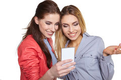 Deux femmes partageant le media social dans un téléphone intelligent Photographie stock libre de droits