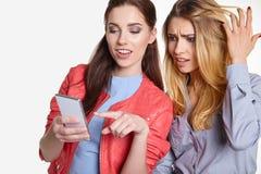 Deux femmes partageant le media social dans un téléphone intelligent Photographie stock