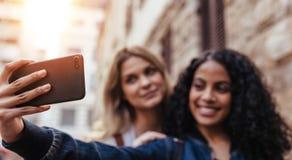 Deux femmes posant pour un selfie dehors Photographie stock libre de droits