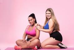 Deux femmes potelées s'asseyant sur le plancher Photographie stock libre de droits