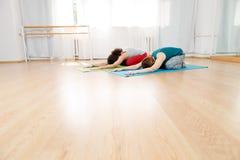 Deux femmes pratiquant l'asana pendant leur classe de yoga dans le studio Photo libre de droits