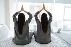 Deux femmes pratiquant le yoga se reposant dans la pose de lotus sur le lit Image libre de droits