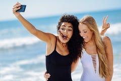 Deux femmes prenant le selfie photographient avec le smartphone dans la plage Photographie stock