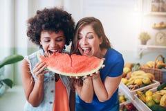 Deux femmes prenant une morsure d'une pastèque Image stock