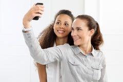 Deux femmes prennent des photos avec votre téléphone Photo libre de droits