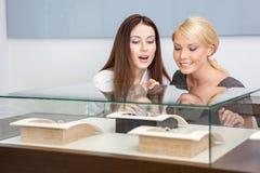 Deux femmes regardant l'étalage avec des bijoux Photographie stock libre de droits