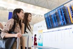 Deux femmes regardant le conseil de numéro de vol Images stock
