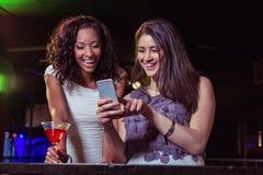 Deux femmes regardant le téléphone portable et souriant au compteur de barre Image libre de droits