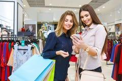 Deux femmes regardant un téléphone portable avec des paniers Images stock