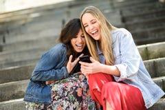 Deux femmes regardant une certaine chose drôle à leur téléphone intelligent Images stock