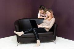Deux femmes regardent un moniteur d'ordinateur portable image stock