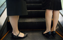 Deux femmes restant sur l'escalator Photographie stock libre de droits