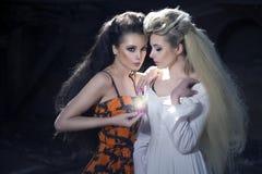 Deux femmes retenant le flacon magique photos stock