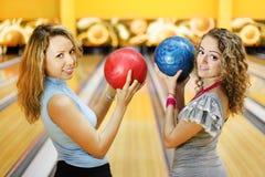 Deux femmes retiennent des billes et sourient dans le club de bowling Photo libre de droits