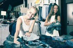 Deux femmes sélectionnant la nouvelle paire de jeans dans le département de mode Photographie stock libre de droits