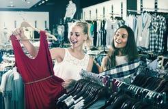 Deux femmes sélectionnant la nouvelle robe dans le département de mode Image stock