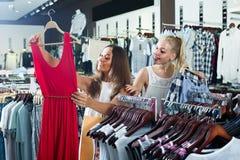 Deux femmes sélectionnant la nouvelle robe dans le département de mode Image libre de droits
