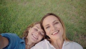 Deux femmes s'étendant sur l'herbe et prendre une photo de selfie ensemble banque de vidéos