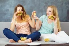 Deux femmes s'asseyant à l'entraîneur mangeant des aliments de préparation rapide photos stock