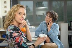Deux femmes s'asseyant à la table en cuisine et café potable Images stock