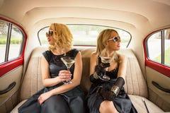 Deux femmes s'asseyant dans la voiture de vintage et ayant des coctails Photos libres de droits
