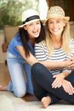 Deux femmes s'asseyant en dehors de la Chambre Photo stock