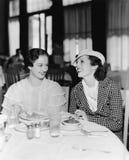 Deux femmes s'asseyant ensemble dans un restaurant (toutes les personnes représentées ne sont pas plus long vivantes et aucun dom Image libre de droits