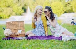 Deux femmes s'asseyant sur la couverture et textoter Photographie stock libre de droits