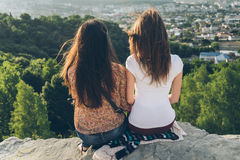 Deux femmes s'asseyant sur la crête et le lookin sur la ville aménagent en parc Image libre de droits