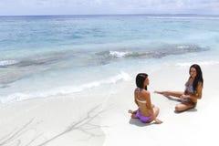 Deux femmes s'asseyant sur la plage Images stock