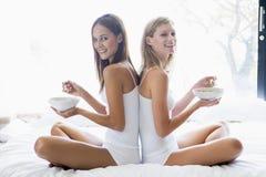 Deux femmes s'asseyant sur le bâti mangeant de la céréale Image stock