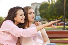 Deux femmes s'asseyant sur le banc Photographie stock libre de droits