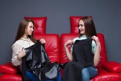 Deux femmes s'asseyant sur le divan et essaye des robes Image stock