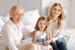 Deux femmes s'asseyant sur le lit avec l'enfant dans l'intervalle Photographie stock