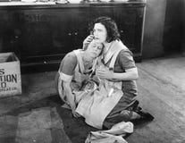 Deux femmes s'asseyant sur le plancher tandis qu'on tient l'autre (toutes les personnes représentées ne sont pas plus long vivant Images stock