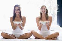 Deux femmes s'asseyant sur le sourire de céréale de consommation de bâti Images stock