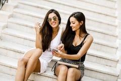 Deux femmes s'asseyant sur les escaliers en dehors de et à l'aide du téléphone portable Photos stock