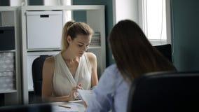 Deux femmes s'asseyant vis-à-vis de l'un l'autre au travail dans le bureau banque de vidéos