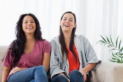 Deux femmes s'asseyent à coté sur des autres sur le divan Photographie stock libre de droits