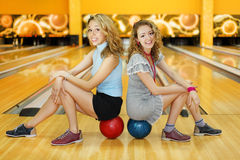 Deux femmes s'asseyent sur des billes et sourient dans le club de bowling Photographie stock