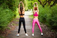 Deux femmes s'exerçant en parc Jeune belle femme faisant des exercices ensemble dehors photographie stock