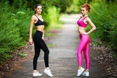 Deux femmes s'exerçant en parc Jeune belle femme faisant des exercices ensemble dehors image libre de droits