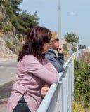 Deux femmes se penchant contre une barrière et examinant la distance Images stock