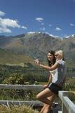 Deux femmes se photographiant contre la barrière de campagne Photographie stock libre de droits