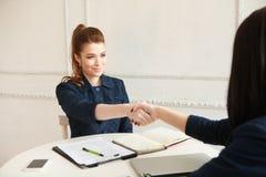 Deux femmes se serrant la main à un bureau Photographie stock libre de droits