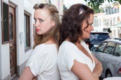 Deux femmes se tenant de nouveau au dos sur la rue de ville Photo libre de droits