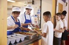 Deux femmes servant la nourriture à un garçon dans une file d'attente de cafétéria de l'école Photo stock